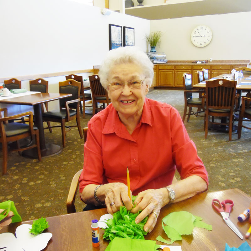 one of trinity village's residents, pat, works on her four leaf clover craft