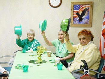 immanuel courtyard residents wave their irish top hats in the air at the camera