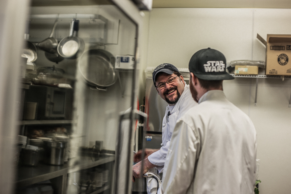 Steven Bock laughs with a fellow cook while washing dishes in the Pacific Springs Village kitchen.