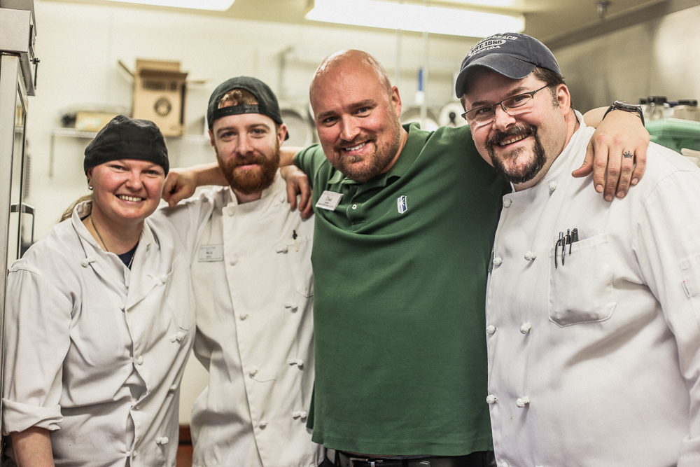 Steven Bock poses with two cooks and lifestyle manager at Pacific Springs Village in the kitchen