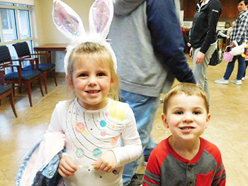two children pose wearing easter attire