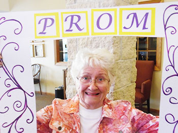 resident poses with prom sign at trinity village