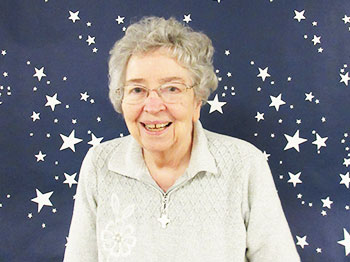 A residents poses in front of a starry background at Immanuel Fontenelle's spring formal