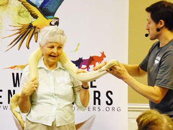 A resident at Pacific Springs Village interacts with a snake at a Wildlife Encounters presentation.