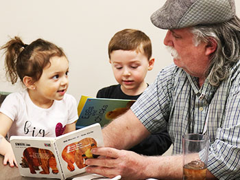 A participant from Immanuel Pathways in central Iowa reads to a child from St. Andrew's Childrens' Program.