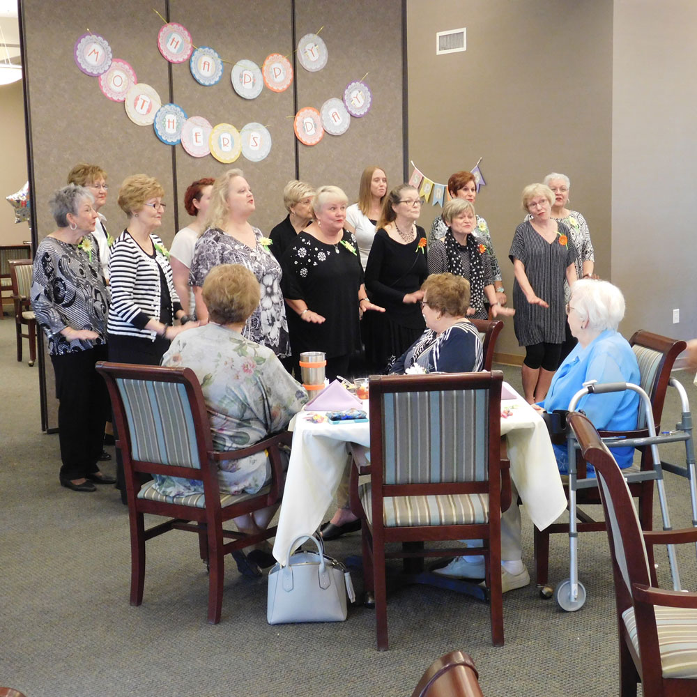 A group of women sing for residents and guests at Clark Jeary's Mother's Day Brunch