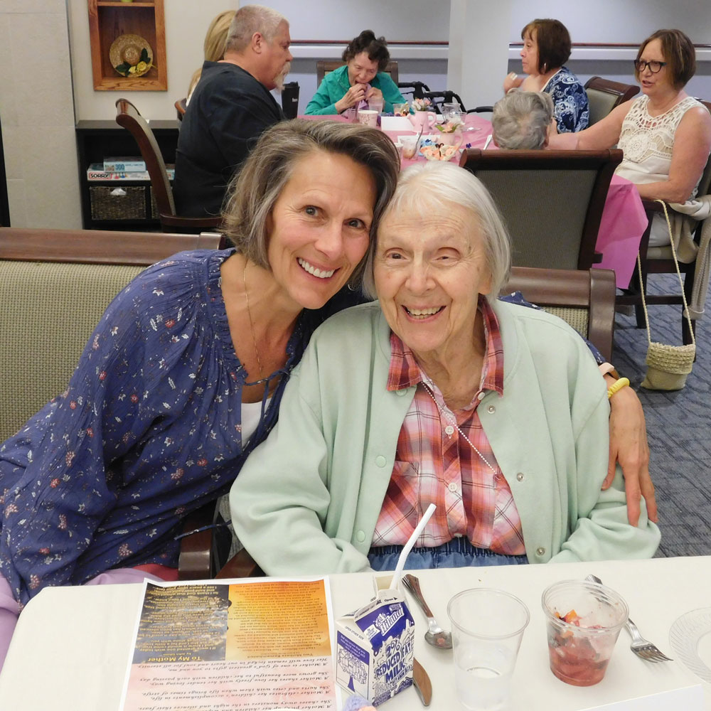 A resident at Clark Jeary in Lincoln, Nebraska poses with her daughter during the senior living community's Mother's Day Brunch