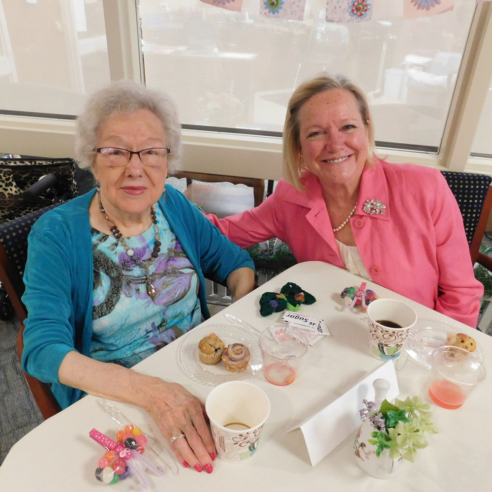 A resident from Clark Jeary in Lincoln, Nebraska smiles with her daughter during the senior living community's Mother's Day Brunch