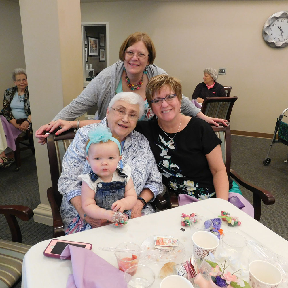 A resident poses with multiple generations of women in her family during Clark Jeary's Mother's Day Brunch in Lincoln, Nebraska