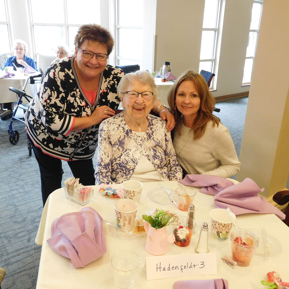 A resident poses with two female family members at Clark Jeary's annual Mother's Day Brunch in Lincoln, Nebraska