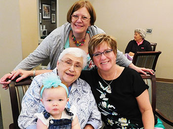 A resident from Clark Jeary, a senior living community in Lincoln, Nebraska, poses with multiple generations of female family members during a Mother's Day Brunch