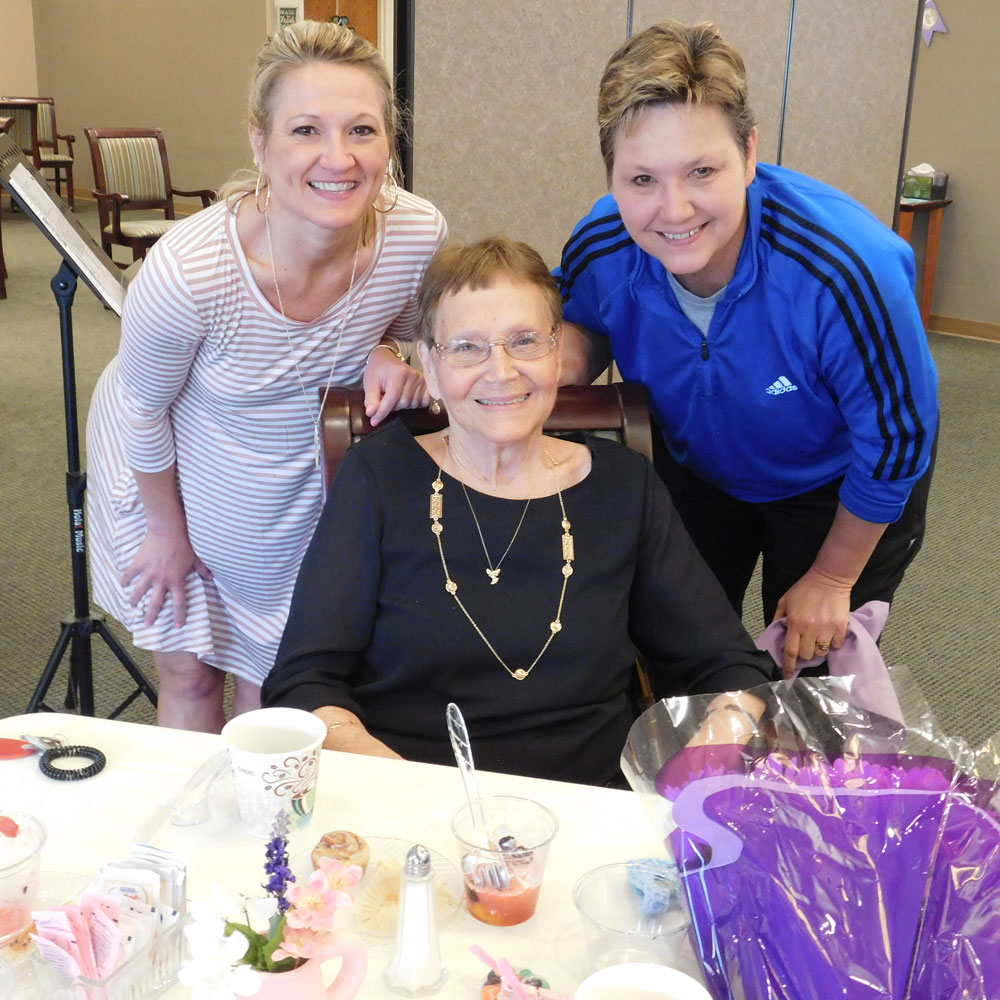 A resident from Clark Jeary, a senior living community in Lincoln, Nebraska, poses with two female family members at a Mother's Day Brunch
