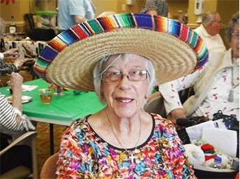 A resident from Immanuel Village, a senior living community in Omaha, Nebraska, smiles while wearing a sombrero in celebration of Cinco De Mayo
