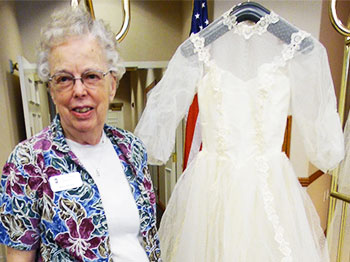 Ann Holmes, resident of The Landing, an Immanuel senior living community in Lincoln, Nebraska, poses with her wedding dress that she donated to a display of historic wedding attire.