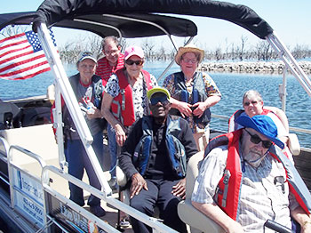 A crew of residents from Immanuel Courtyard, an Immanuel senior living community in Omaha, Nebraska, smile while floating on a pontoon with their fishing gear provided by the organization Live Well. Go Fish., a non-profit that offers fishing excursions for seniors.