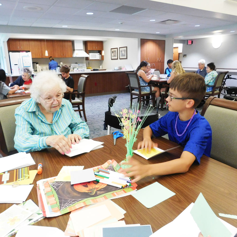 A resident from Clark Jeary, an Immanuel senior living community in Lincoln, Nebraska, creates cards with a boy from Trinity Daycare during one of the community's intergenerational activities.