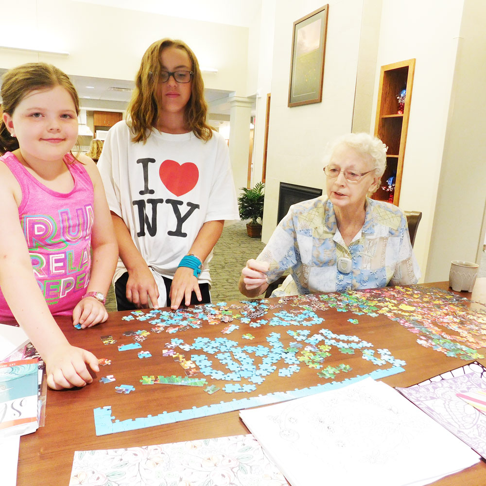 Kids from Trinity Daycare create cards with a resident from Clark Jeary, a senior living community in Lincoln, Nebraska, during one of the community's intergenerational activities.