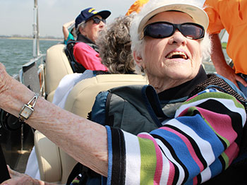 A Lakeside Village resident looks up into the sky as she holds her fishing rod over the side of a pontoon boat.