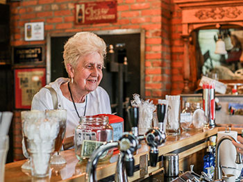 A resident from Pacific Springs Village, an Immanuel senior living community, happily watches her ice cream sundae being made while at the Springfield Old Fashioned Soda Fountain in Springfield, Nebraska.